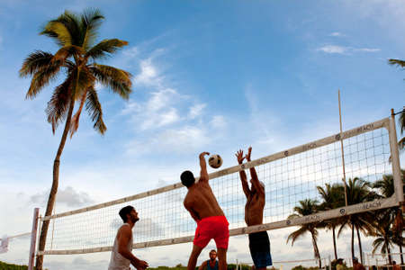 in the sand: Miami, FL, USA - December 27, 2014:  A man tries to spike the ball past a blocker playing in a pickup game of beach volleyball on a public beach off Ocean Drive in Miami. Editorial