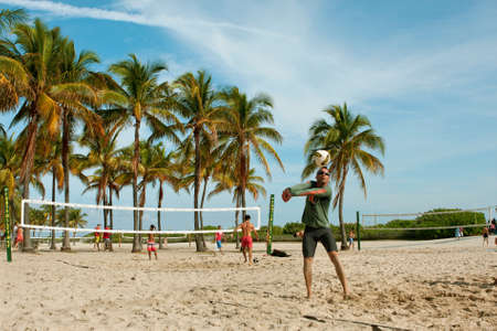 sun drenched: Miami, FL, USA - December 27, 2014:  People play pickup games of beach volleyball on a public beach off Ocean Drive in Miami.