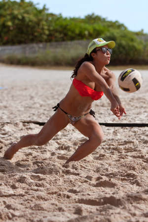 skillfully: Miami, FL, USA - December 27, 2014:  A young woman skillfully passes a volleyball in a pickup game of beach volleyball on a public beach off Ocean Drive in Miami.