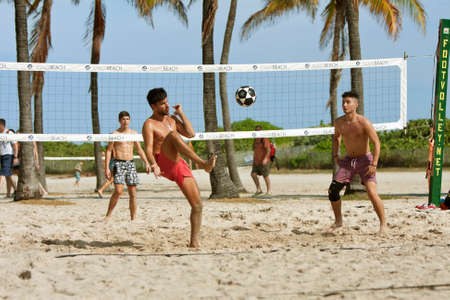 Miami, FL, USA - December 27, 2014:  Young men kick a soccer ball over the net while playing foot volley on the beach volleyball courts at a public beach off Ocean Drive in Miami.