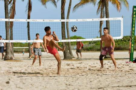pies: Miami, FL, EE.UU. - 27 de diciembre 2014: Los hombres j�venes patear un bal�n de f�tbol en la red mientras jugaba voleibol pie en las canchas de voleibol de playa en una playa p�blica de Ocean Drive, en Miami.
