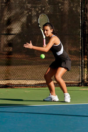 mach: A female high school tennis player prepares to hit forehand in a mach Stock Photo