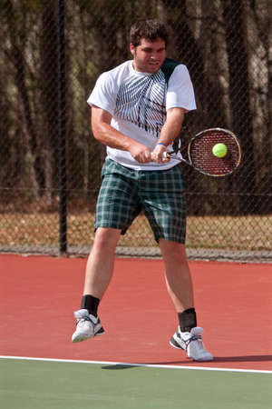 backhand: A male high school tennis player hits a powerful twohanded backhand during a match as the ball freezes on the racket head.