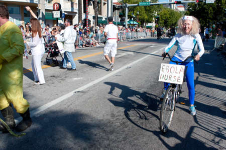 oddball: Miami FL USA  December 28 2014:  A senior woman poses as an ebola nurse riding a bicycle while participating in the annual Mango Strut parade in Coconut Grove.