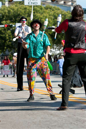 people street: Miami FL USA  December 28 2014:  Jugglers perform along the parade route of the annual Mango Strut parade in Coconut Grove.