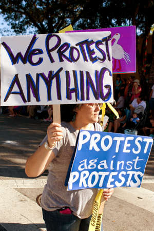 commentary: Miami FL USA  December 28 2014:  A selfproclaimed protester against protests holds signs in the Miami Mango Strut parade. Editorial