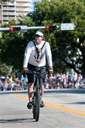 oddball: Miami FL USA  December 28 2014:  A man rides a bicycle with a chihuahua strapped to his chest as he surveys the parade route of the annual Mango Strut parade in Coconut Grove.