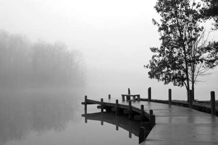 dreary: A thick blanket of fog covers a wooden deck and lake on a cold winter day. Stock Photo