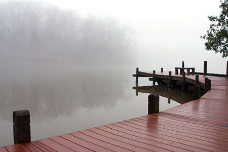 dreary: Fog covers a lake and wooden deck on a dreary winter day. Stock Photo