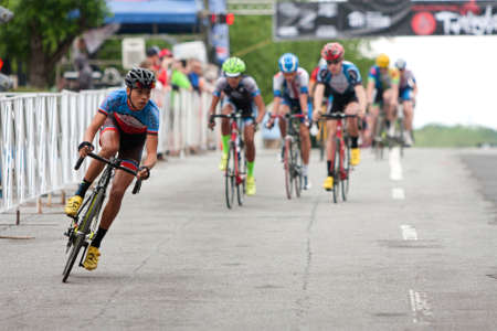 adrenaline rush: Athens, GA, USA - April 25, 2015:  Teenage cyclists compete in an amateur race on the streets of downtown Athens, in the annual Twilight Criterium bike races on April 25, 2015 in Athens, GA. Editorial