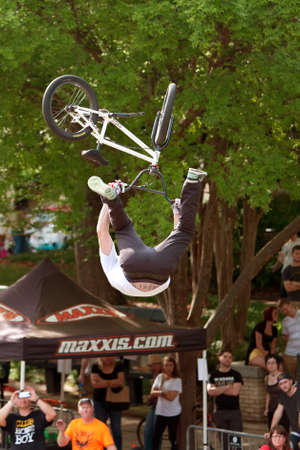 Athens, GA, USA - April 25, 2015:  Young BMX pro flips upside down performing trick in the pro BMX competition at the annual Athens Twilight Criterium, on April 25, 2015 in Athens, GA.