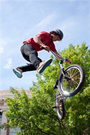 adrenaline rush: Athens, GA, USA - April 25, 2015:  Teenager performs midair stunt in the pro BMX competition at the annual Athens Twilight Criterium, on April 25, 2015 in Athens, GA. Editorial