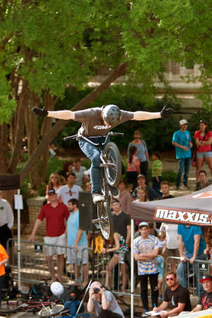Athens, GA, USA - April 25, 2015:  Young BMX pro lets go of handlebars while performing a trick in the pro BMX competition at the annual Athens Twilight Criterium, on April 25, 2015 in Athens, GA.