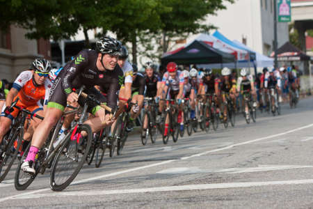 adrenaline rush: Athens, GA, USA - April 25, 2015:  A male cyclist leans into a turn as he leads a large group while racing in an amateur race on the streets of downtown Athens, in the annual Twilight Criterium.