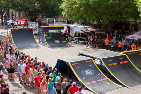 adrenaline rush: Athens, GA, USA - April 25, 2015:  A large crowd watches a young BMX pro perform spectacular tricks in the pro BMX competition at the annual Athens Twilight Criterium, on April 25, 2015 in Athens, GA. Editorial