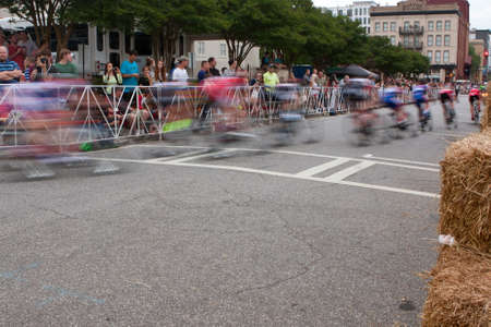 bunched: Athens, GA, USA - April 25, 2015:  Motion blur of group of male cyclists turning a corner in an amateur race on city streets, in the annual Athens Twilight Criterium.