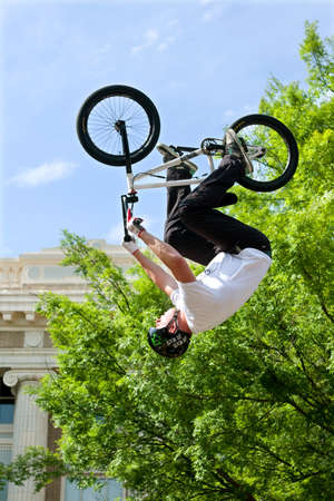 adrenaline rush: Athens, GA, USA - April 25, 2015:  Young adult performs upside-down stunt in the pro BMX competition at the annual Athens Twilight Criterium, on April 25, 2015 in Athens, GA. Editorial