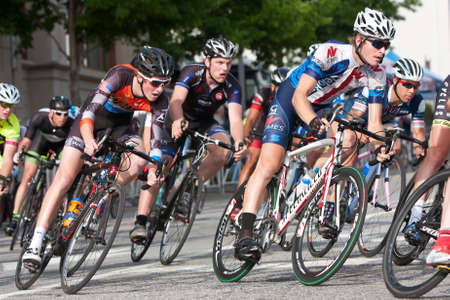 Athens, GA, USA - April 25, 2015:  A tightly packed group of male cyclists lean into a turn while racing in an amateur race on the streets of downtown Athens, in the annual Twilight Criterium.