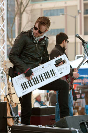 Hampton, GA, USA - February 28, 2015:  An alternative rock musician holds a Roland Lucina synthesizer like a guitar while playing in a concert outside Atlanta Motor Speedway before a race. Editorial