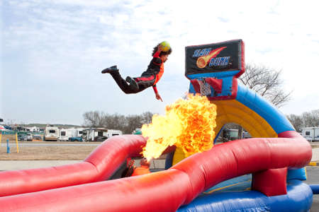 Hampton, GA, USA - February 28, 2015:  One man breathes a huge fireball while another uses a trampoline to jump over the flames to dunk a ball in a carnival act.