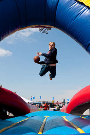 adrenaline rush: Hampton, GA, USA - February 28, 2015:  A teenager uses a mini-trampoline to get airborne while  attempting to dunk a basketball in a carnival game. Editorial