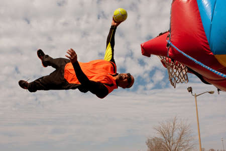 adrenaline rush: Hampton, GA, USA - February 28, 2015:  An entertainer uses a mini-trampoline to get parallel to the ground  in midair, attempting to dunk a ball in a basketball hoop, at a carnival act.