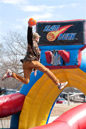 adrenaline rush: Hampton, GA, USA - February 28, 2015:  A teenager uses a mini-trampoline to soar above the rim while  attempting to dunk a basketball in a carnival game. Editorial