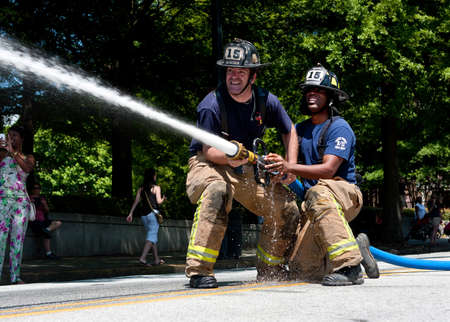 fireman: Atlanta, GA, USA - May 2, 2015:  Firemen steady a hose while aiming at a target in a fireman muster competition between local area fire departments, at the Fire In The Fourth festival in Atlanta. Editorial