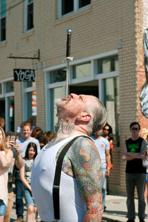 sword act: Atlanta, GA, USA - May 2, 2015:  A freak show artist carefully swallows a sword in front of an audience, while performing at the Fire In The Fourth festival in Atlanta. Editorial