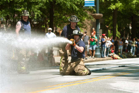 fireman helmet: Atlanta, GA, USA - May 2, 2015:  Firemen aim a fire hose at a target in a fireman muster competition between local area fire departments, at the Fire In The Fourth festival in Atlanta.