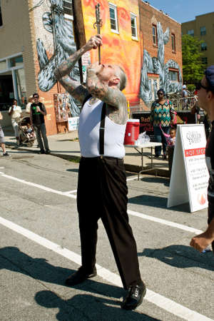 sword act: Atlanta, GA, USA - May 2, 2015:  A freak show artist carefully guides two swords down his throat , while performing at the Fire In The Fourth festival in Atlanta.