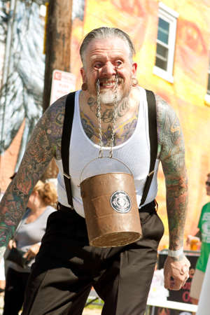 expertise: Atlanta, GA, USA - May 2, 2015:  A man swings a bucket filled with bricks, by using chains hooked to the inside of his eyelids, while performing in a freak show at the Fire In The Fourth festival in Atlanta.
