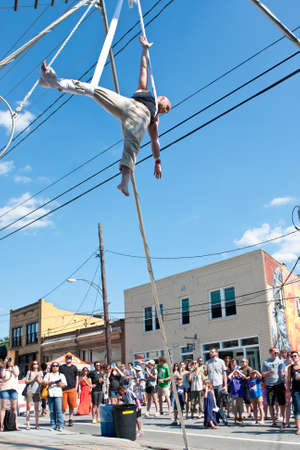 adrenaline rush: Atlanta, GA, USA - May 2, 2015:  A man suspends himself with fabric ribbons as he performs an aerial show with the Imperial OPA Circus at the Fire In The Fourth festival in Atlanta. Editorial