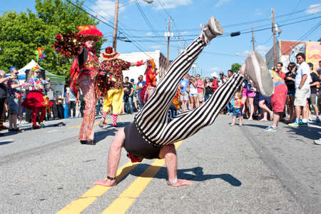 adrenaline rush: Atlanta, GA, USA - May 2, 2015:  A man suspends himself off the pavement by doing an impromptu handstand in the street at the Fire In The Fourth festival in Atlanta. Editorial