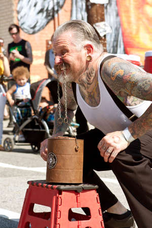 adrenaline rush: Atlanta, GA, USA - May 2, 2015:  A man attempts to lift a bucket full of bricks, by using chains hooked to the inside of his eyelids, while performing in a freak show at the Fire In The Fourth festival in Atlanta.