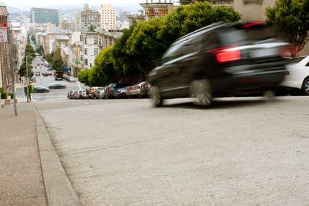 braking: San Francisco, CA, USA - May 18, 2015:  A car motion blurs while braking down a steep hill in the Nob Hill area of San Francisco.