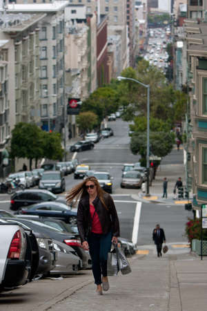 San Francisco, CA, USA - May 18, 2015:  A young woman carrying shopping bags climbs a very steep set of concrete steps in the Nob Hill area of San Francisco.