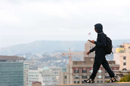 ca he: San Francisco, CA, USA - May 18, 2015:  A young adult male listens to his smart phone as he crosses a street overlooking a steep dropoff in the Knob Hill area of San Francisco. Editorial