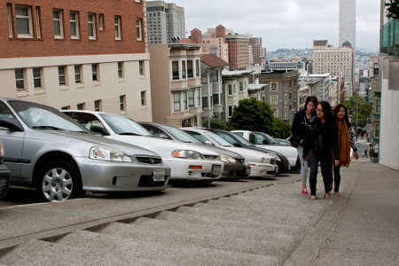 San Francisco, CA, USA - May 18, 2015:  Young Asian women climb a very steep set of concrete steps in the Nob Hill area of San Francisco.
