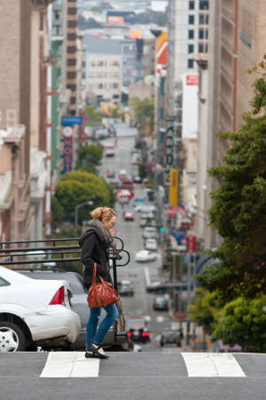 dropoff: San Francisco, CA, USA - May 18, 2015:  The steep hills of San Francisco are evident as a young woman crosses a street overlooking a severe dropoff, in the Nob Hill area of the city.