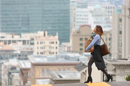 san francisco: San Francisco, CA, USA - May 18, 2015:  A young, fashionable woman carries a bag of groceries across the street in a highly elevated, scenic area of San Francisco.