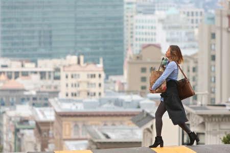San Francisco, CA, USA - 18 mei 2015: Een jonge, modieuze vrouw draagt een tas met boodschappen overkant van de straat in een sterk verhoogde, schilderachtige omgeving van San Francisco.