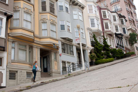 San Francisco, CA, USA - May 18, 2015:  A woman walks up a very steep hill in the Nob Hill area of San Francisco.
