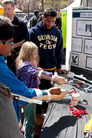overcoming adversity: Atlanta, GA, USA - March 28, 2015:  Kids attempt to drop bottle caps into a cup using a prosthetic arm and hooks, at a Georgia Tech prosthetics exhibit at the Atlanta Science Fair in Centennial Park in Atlanta.