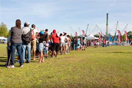 fila de personas: Atlanta, GA, EE.UU. - 11 de abril de 2015: Los padres y los niños se colocan en una línea muy larga esperando su turno para el viaje salto bungy en el Festival de Atlanta Dogwood en Piedmont Park. Editorial