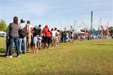 file d attente: Atlanta, GA, USA - 11 Avril, 2015: Les parents et les enfants sont dans une très longue ligne qui attendent leur tour pour le tour de saut à l'élastique au Festival du cornouiller Atlanta en Piedmont Park.
