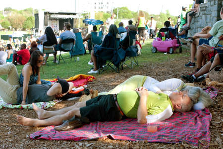 snoozing: Atlanta, GA, USA - April 11, 2015:  A senior couple naps peacefully on a blanket surrounded by hundreds of people in Piedmont Park attending the Atlanta Dogwood Festival.