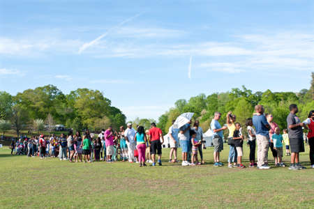 Atlanta, GA, USA - April 11, 2015:  An endless line of parents waits with their kids for their turn on the bungee jumping ride at the Atlanta Dogwood Festival at Piedmont Park.