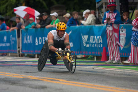 Atlanta, GA, USA - July 4, 2015:  An athlete competing in the wheelchair portion of the Peachtree Road Race speeds toward the finish line in the annual Atlanta Independence Day event. 報道画像