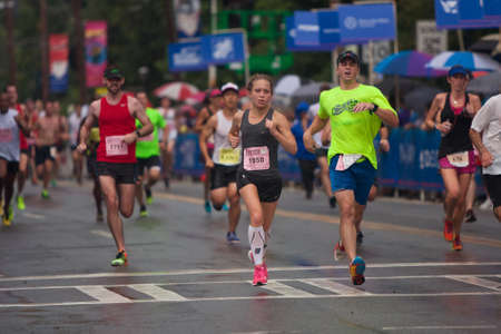 adrenaline rush: Atlanta, GA, USA - July 4, 2015:  Exhausted runners cross the finish line in the rain at the 46th annual Peachtree Road Race 10K in Atlanta. Editorial
